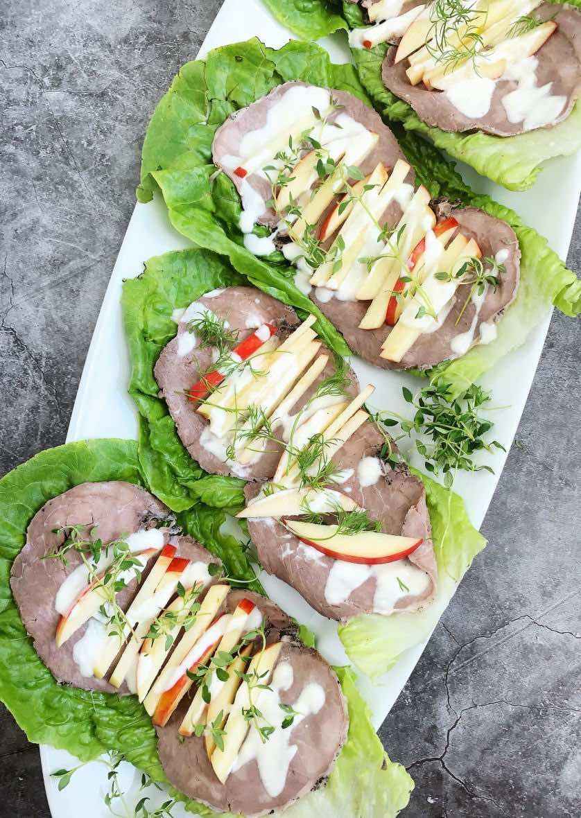 roast beef lettuce wraps topped with red apples, mayonnaise, and fresh herbs, all served on a white platter.