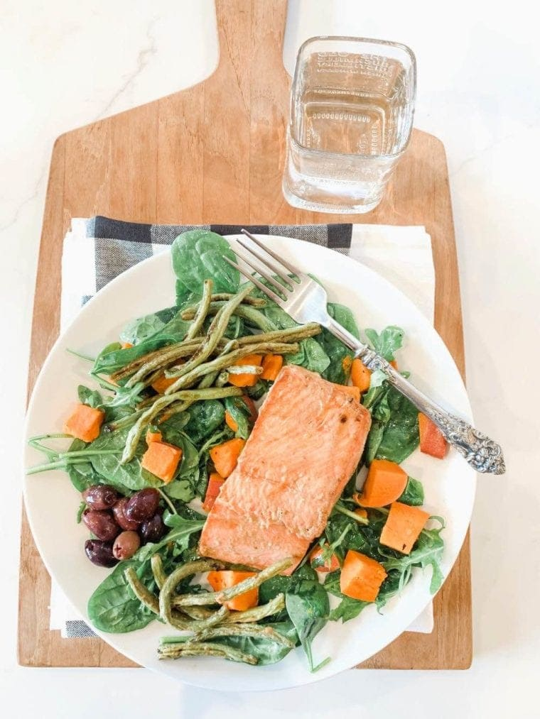 Miso Maple Broiled Salmon Nicoise Salad on a white plate and wooden cutting board.