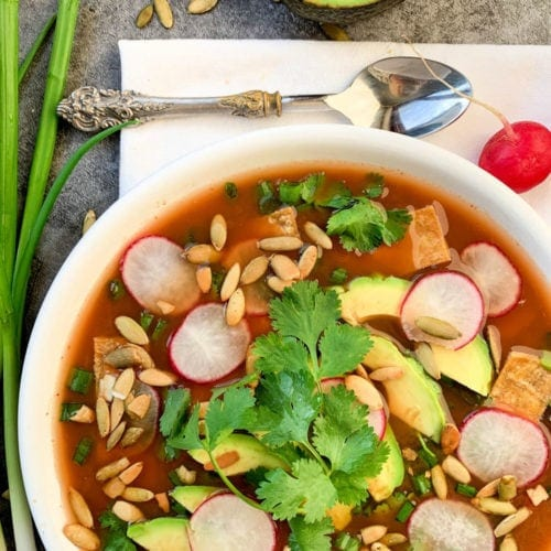 vegan tortilla soup in a white bowl with cilantro and avocado