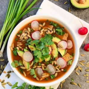 Overhead shot of a bowl of vegan tortilla soup topped with cilantro, avocado, radishes, and pumpkin seeds.