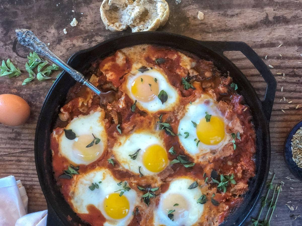 easy shakshuka recipe with tomatoes and chickpeas in a cast iron pan