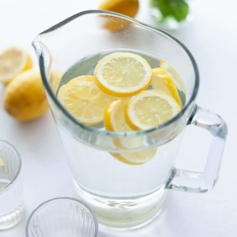 water in a glass pitcher with lemon slices