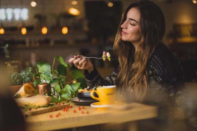 Photo of a woman eating a salad.
