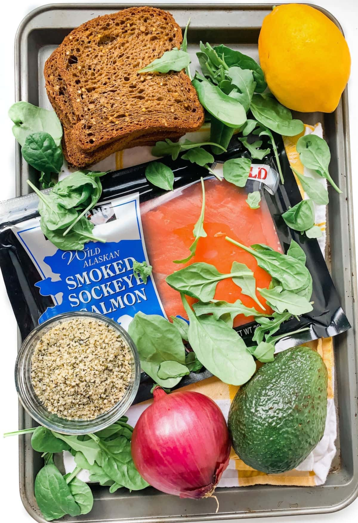 Ingredients on a sheet pan for making a smoked salmon sandwich. These include gluten free bread, leafy greens, smoked salmon, red onion, avocado, hemp seeds, and lemon.