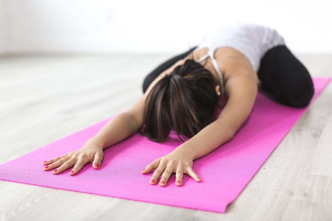 woman doing child pose on a pink yoga mat