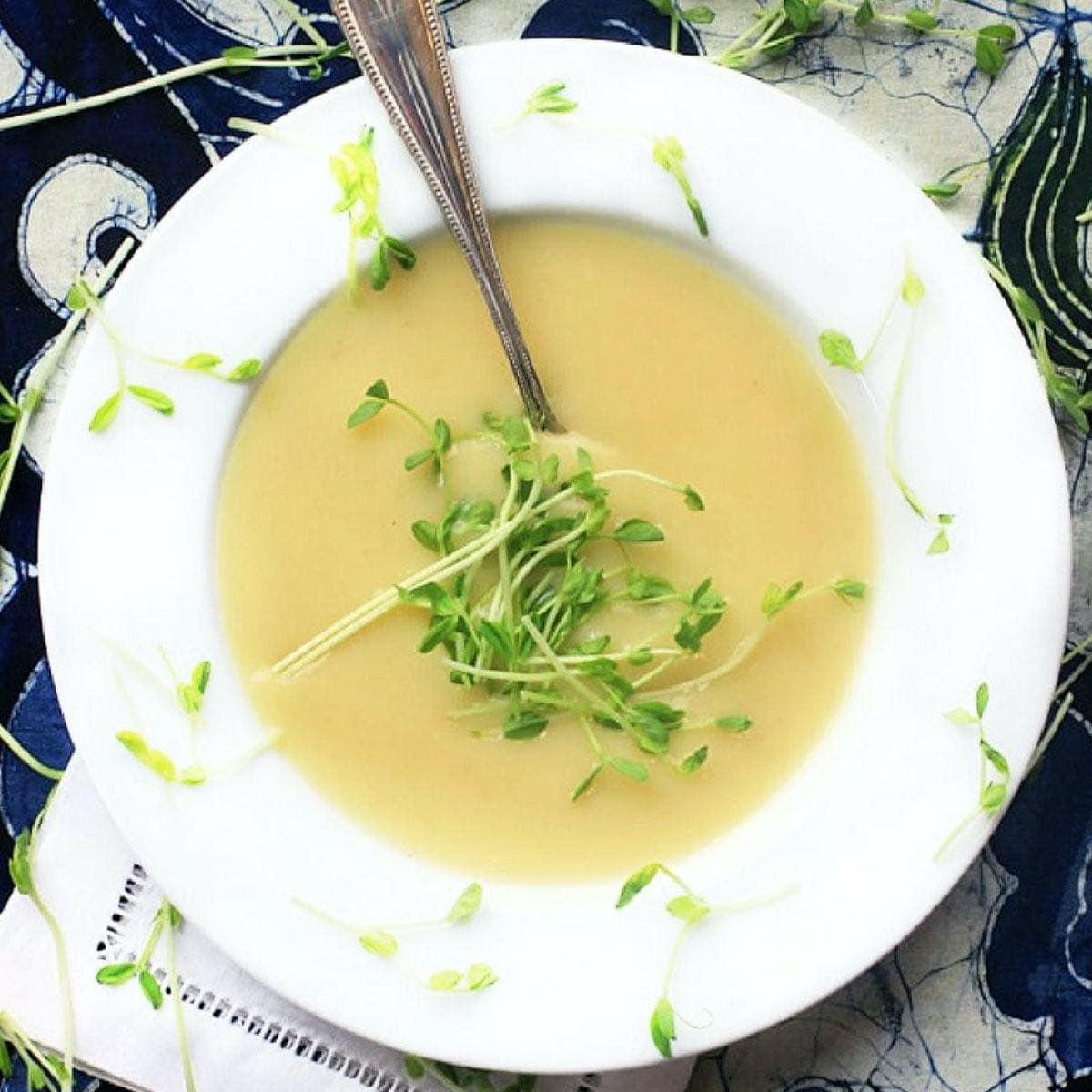 White bowl of potato leek soup on a blue background.