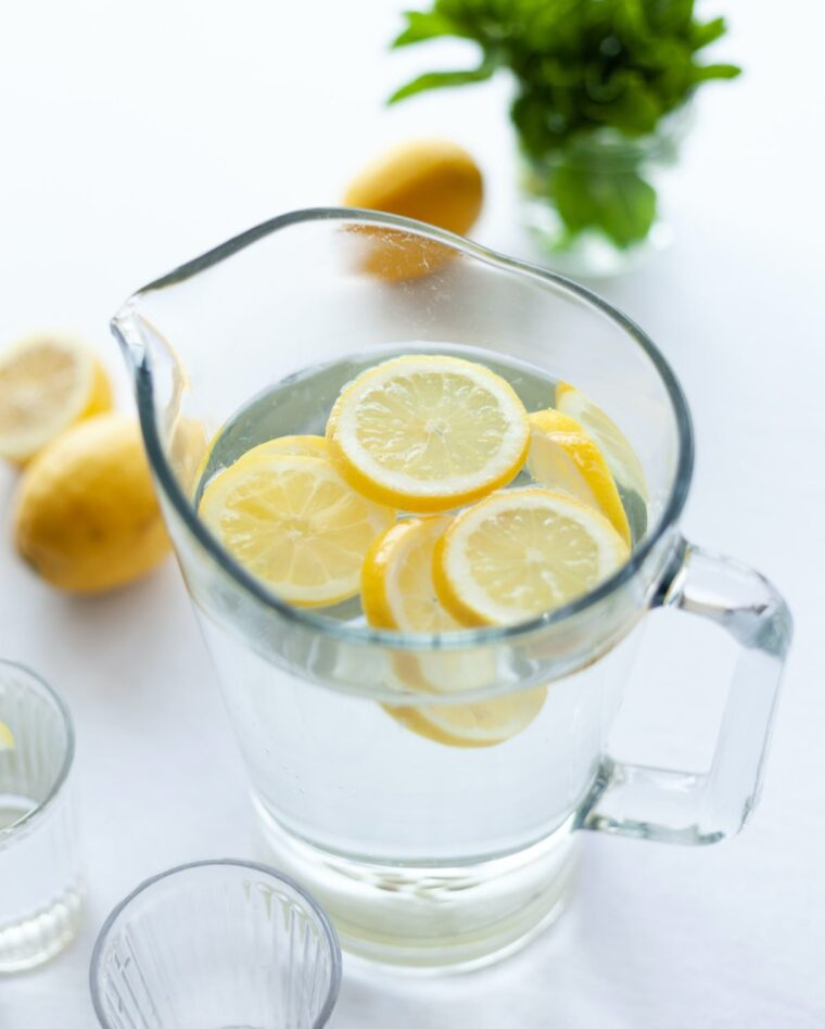 lemon water in a glass pitcher to improve digestion.