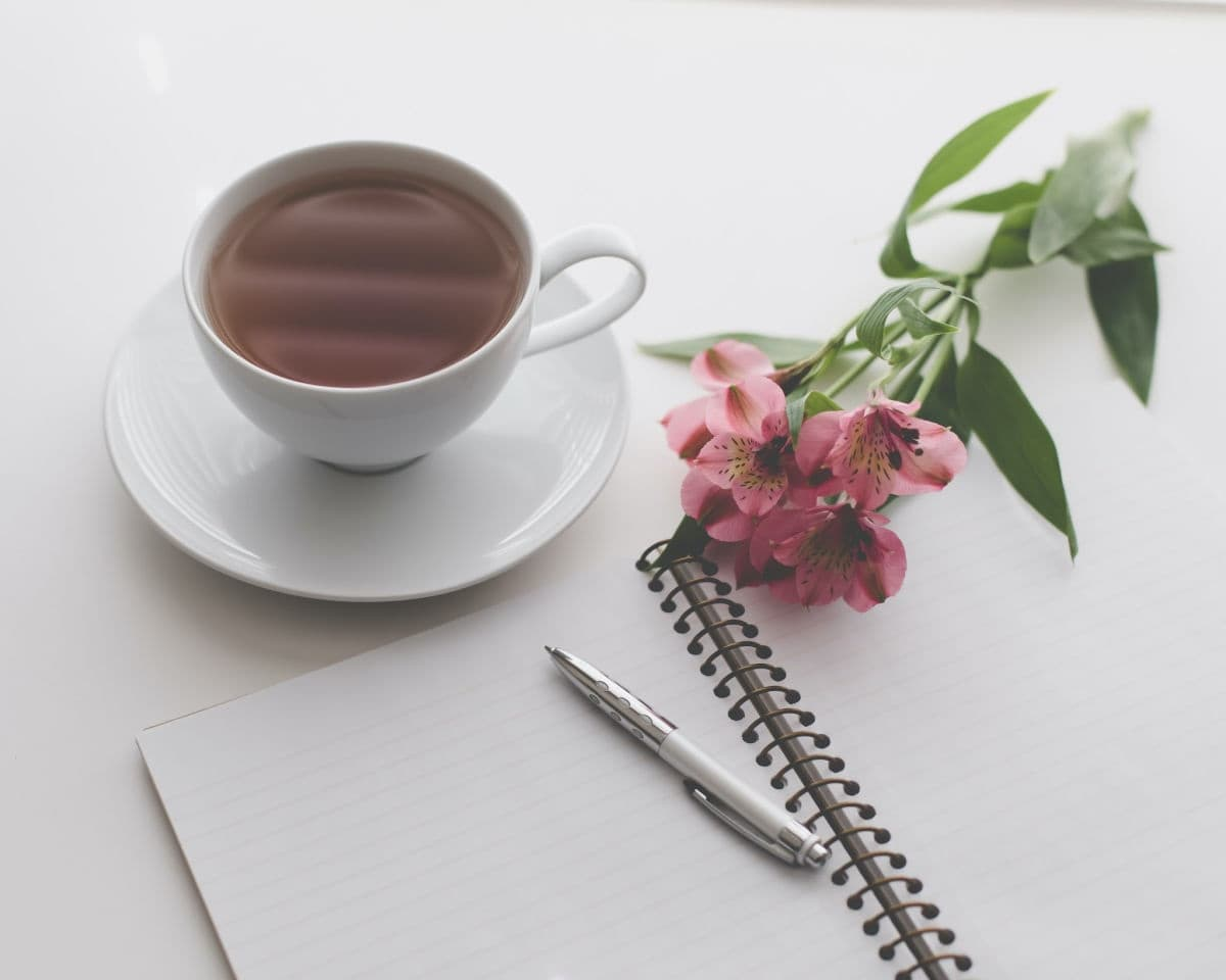 blank journal, cup of coffee, and pink flowers on a table