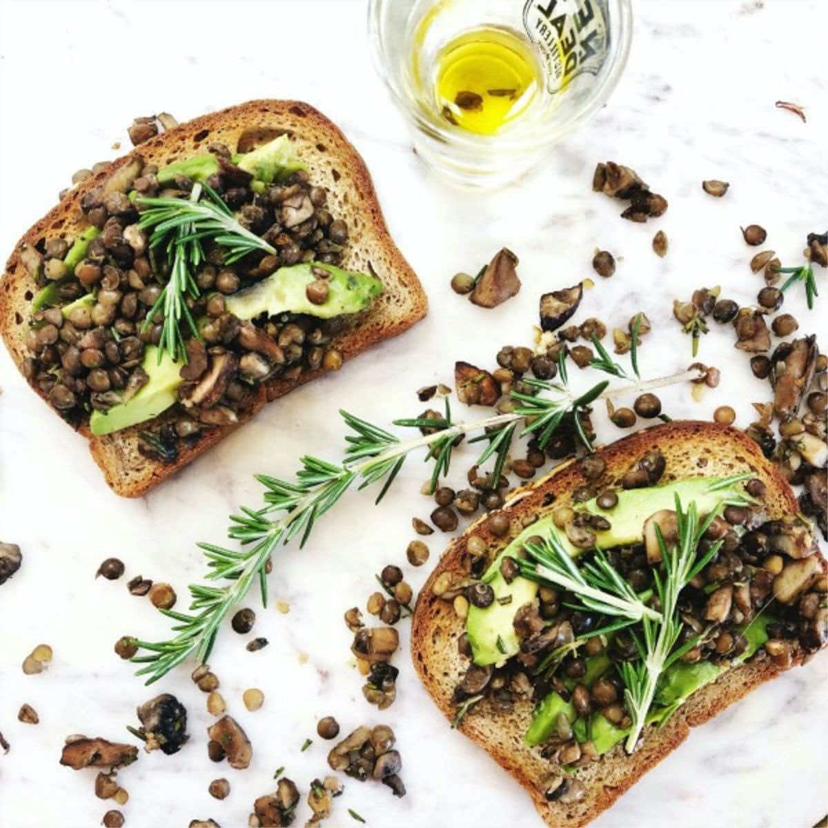 avocado toast with lentils, rosemary, and mushrooms on top of gluten free bread.