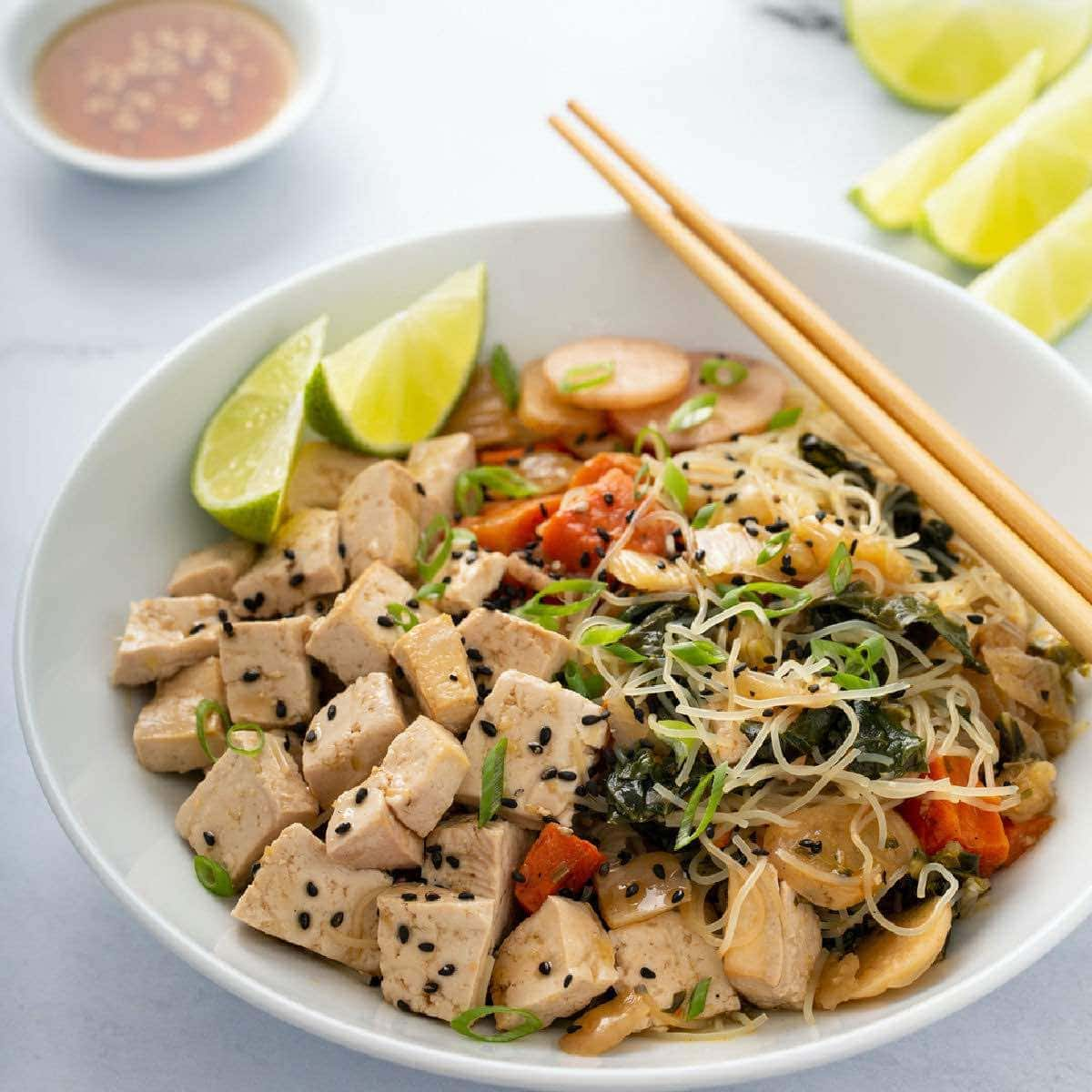 Low FODMAP meal delivery - chicken and vegetables in a white bowl with chopsticks on the rim of the bowl.