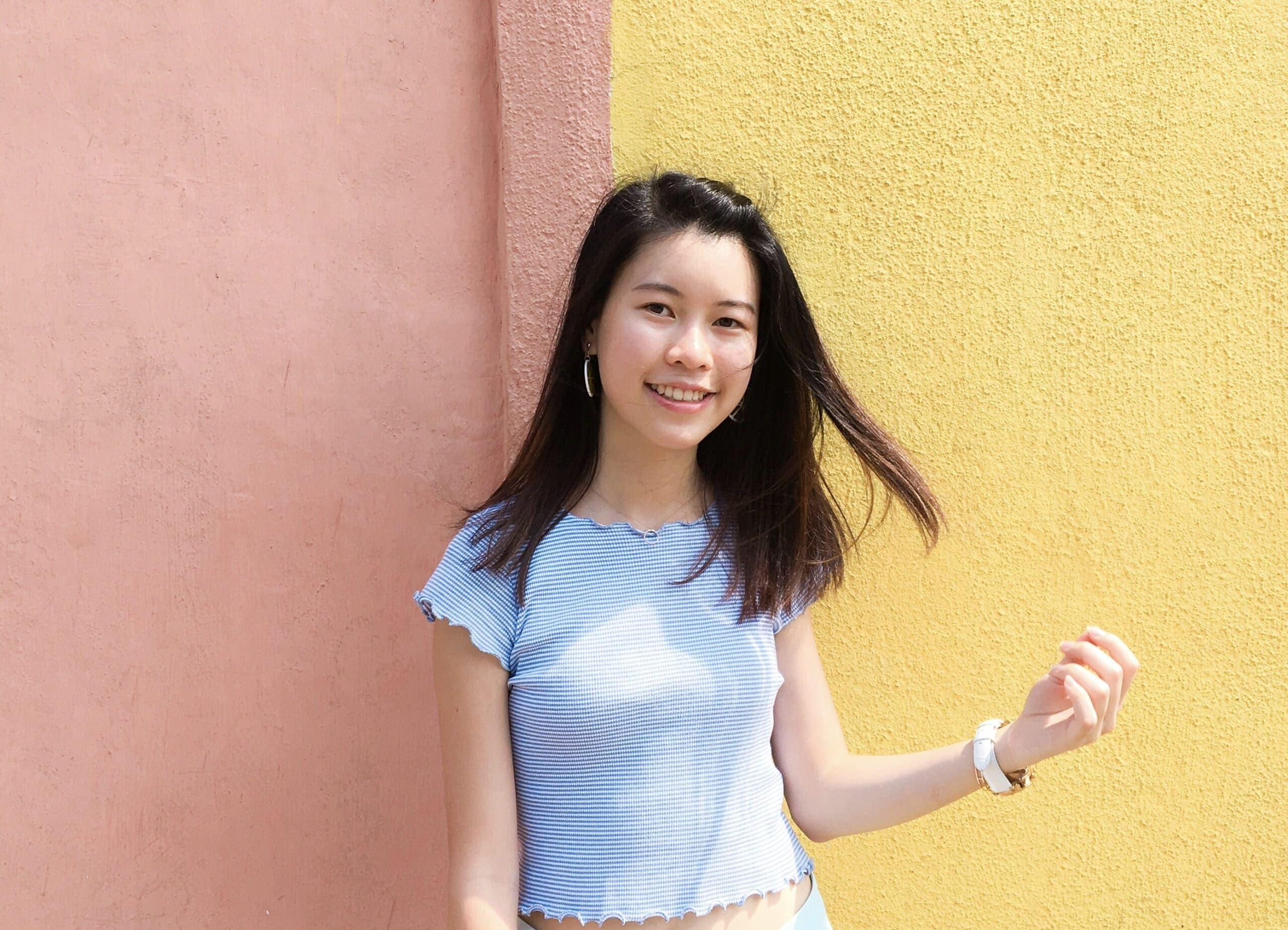 Picture of Yasmine Cheang in front of a pink and yellow background.
