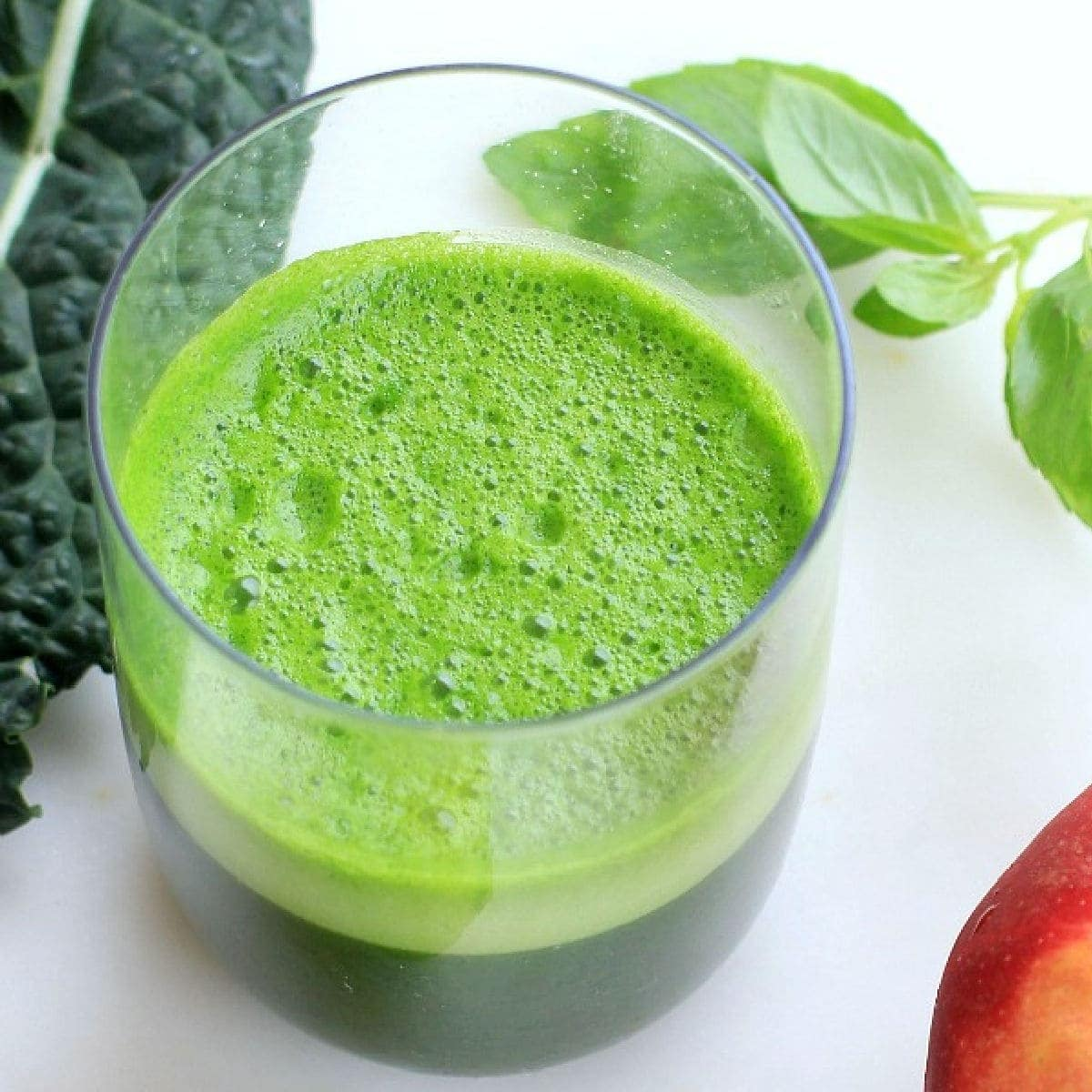 Green juice in a glass with kale and a red apple in the background.