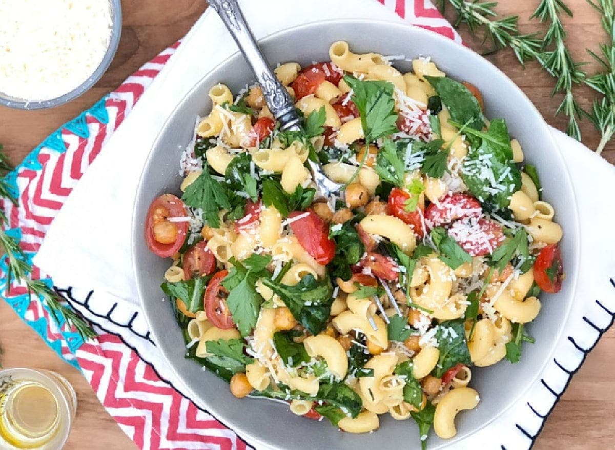 bowl of pasta with herbs, tomatoes, chickpeas, and parmesan cheese.