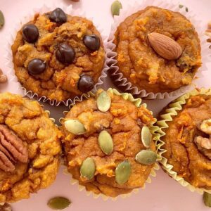 5 paleo pumpkin muffins with varios toppings including pumpkin seeds, pecans, almonds, and chocolate chips