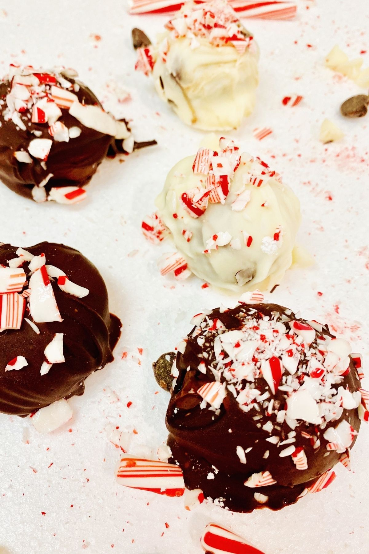 Chocolate Peppermint Vegan Truffles coated with candy canes on a white background.