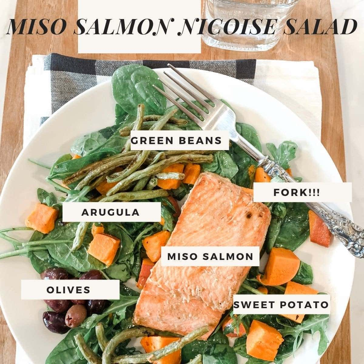 Miso Salmon Salad on a white plate with sweet potatoes, arugula, green beans, and olives.