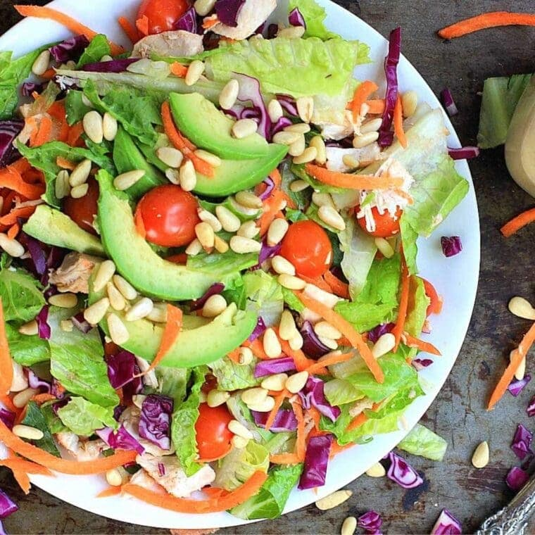 colorful healthy new year salad with avocado, tomato, lettuce, pine nuts, and red cabbage.