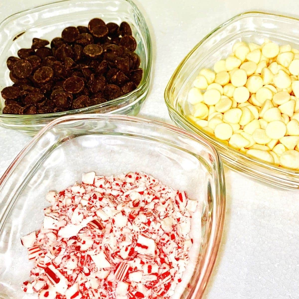 chopped candy canes and chocolate chips in glass bowls.