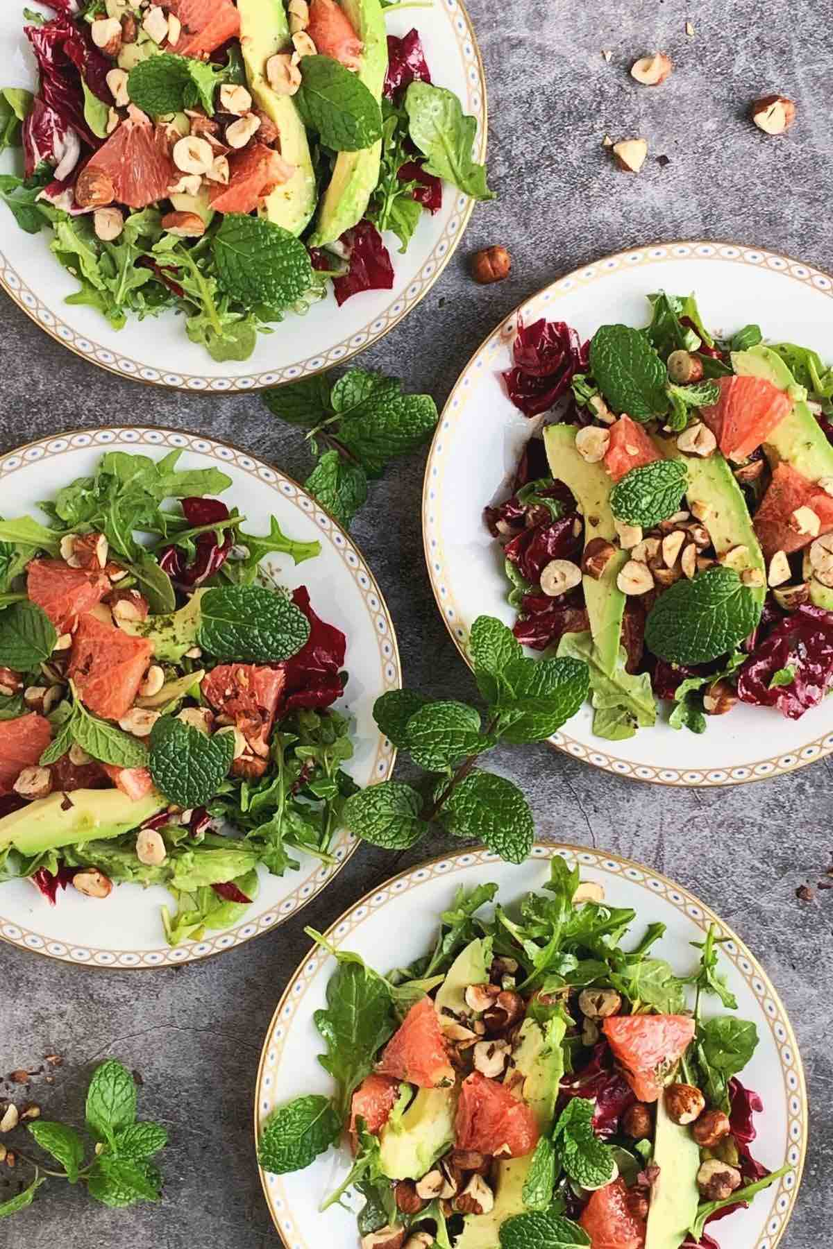4 white plates on a grey backdrop with grapefruit salad.