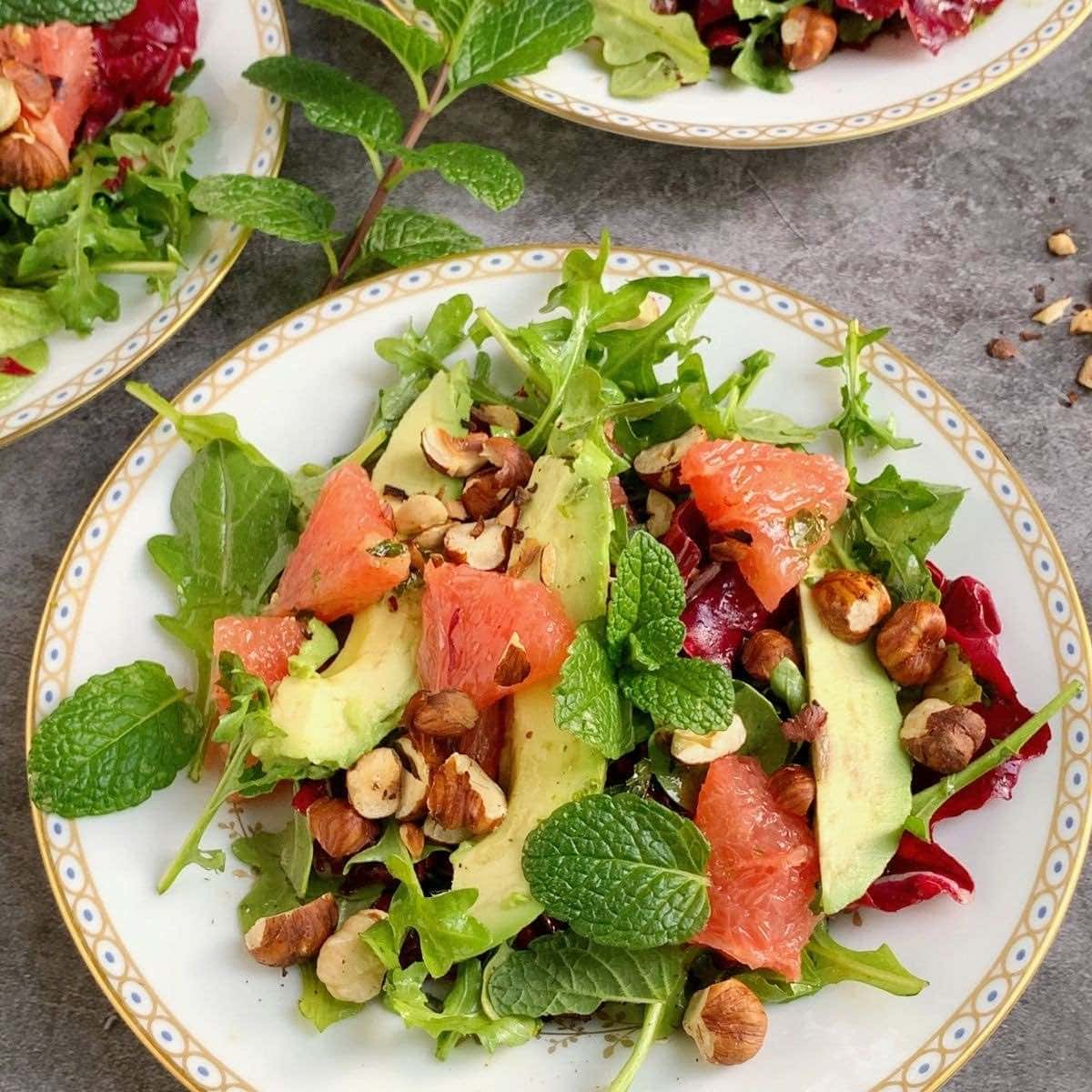 Grapefruit salad on a white plate topped with avocado and hazelnuts.