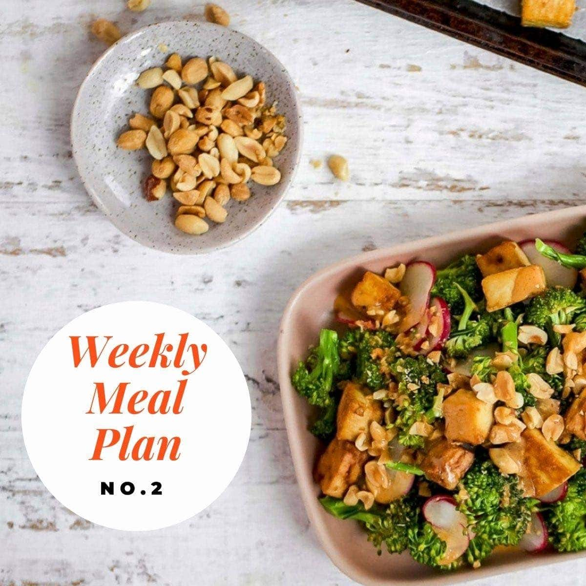 Broccoli peanut tofu salad in a pink sih on a white background and text overly-weekly meal plan no 2.