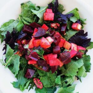 Beet apple walnut salad on top of greens in a white bowl.