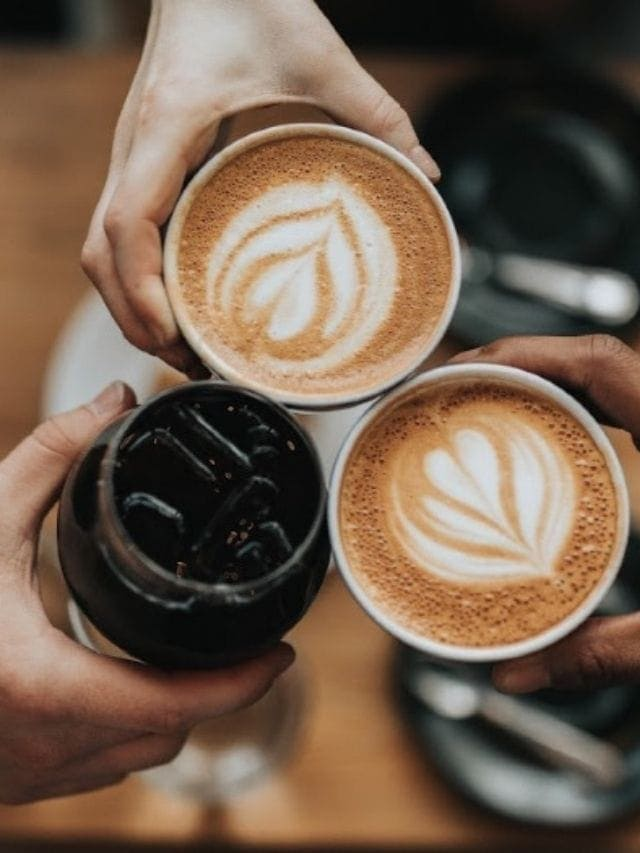 Overhead shot of 3 hand holding cups of coffee.