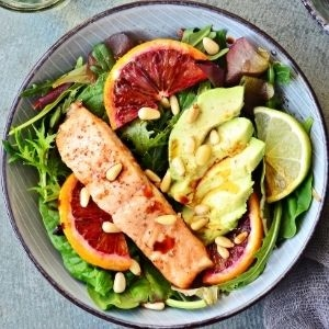 Plate topped with greens, orange slices, salmon, and avocado for a diabetes meal plan.