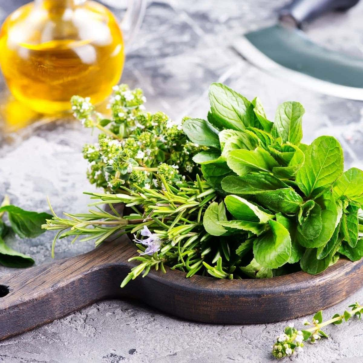 Round wooden cutting board with a variety of fresh herbs and a bottle of oil in the background.