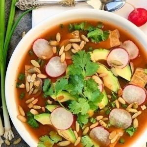 Bowl of tortilla soup topped with pumpkin seeds, radishes, avocado, and cilantro for a simple eats meal plan.