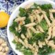 White plate of kale pasta salad on a blue and white tile background.