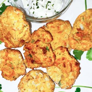 Air Fryer Falafel on a white plate with a bowl of tzatziki sauce.