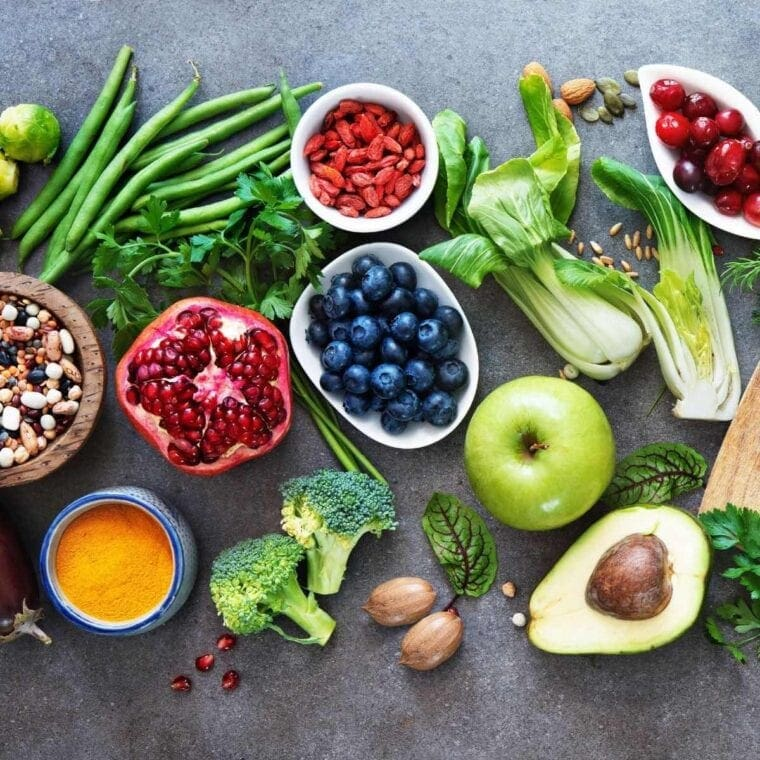 Grey background with a variety of colorful plant based foods including pomegranate, blueberries, green beans, broccoli, beans, and more.