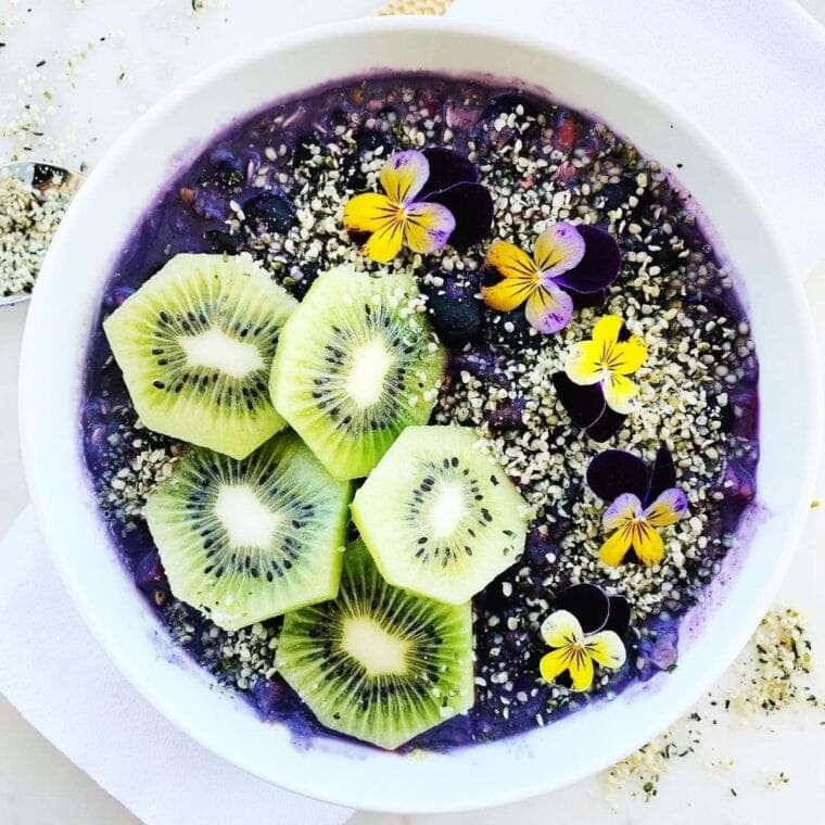 Vegan blueberry smoothie bowl topped with kiwi fruit, hemp seeds, and viola flowers.