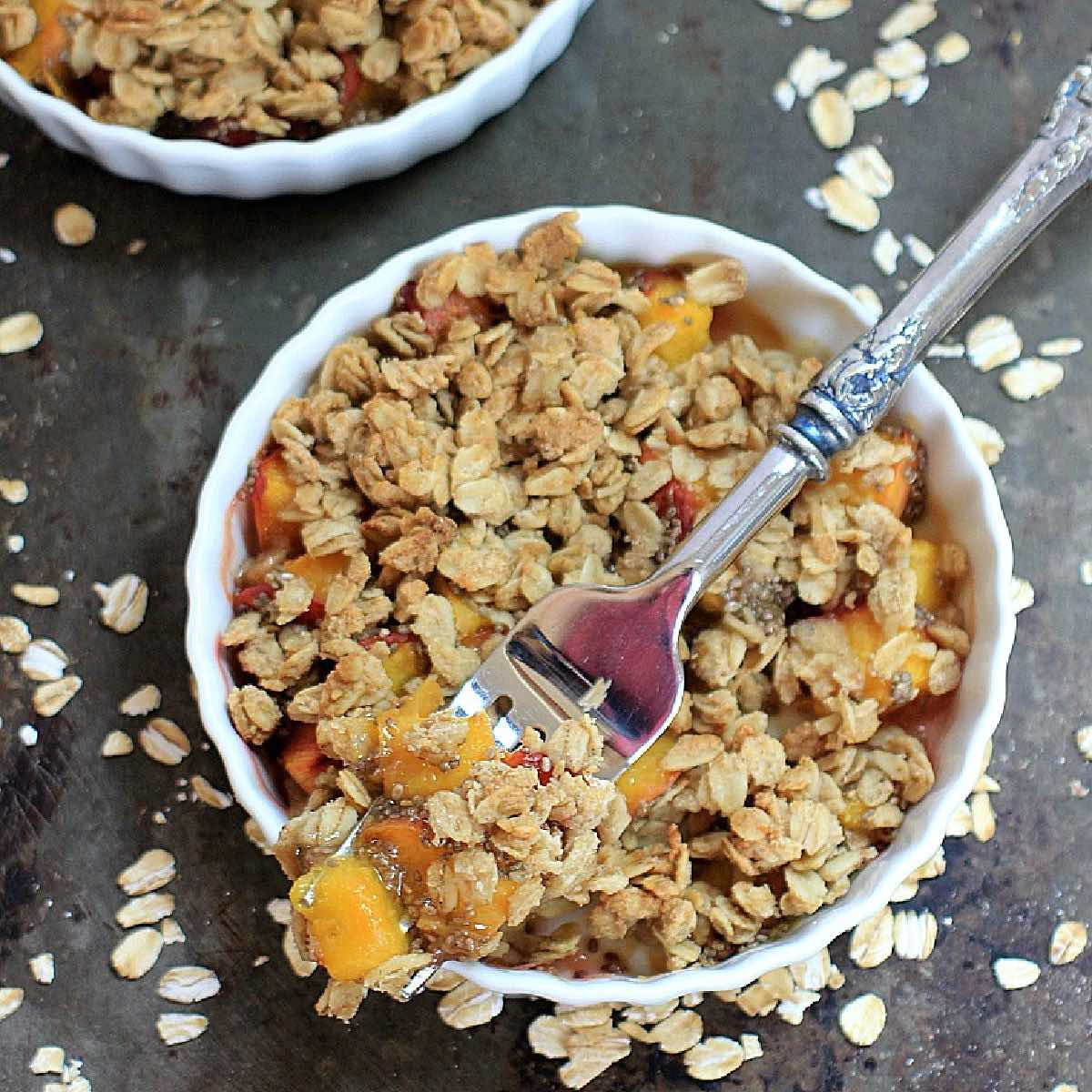 Overhead shot of a gluten free peach crisp in a white dish with a grey background.
