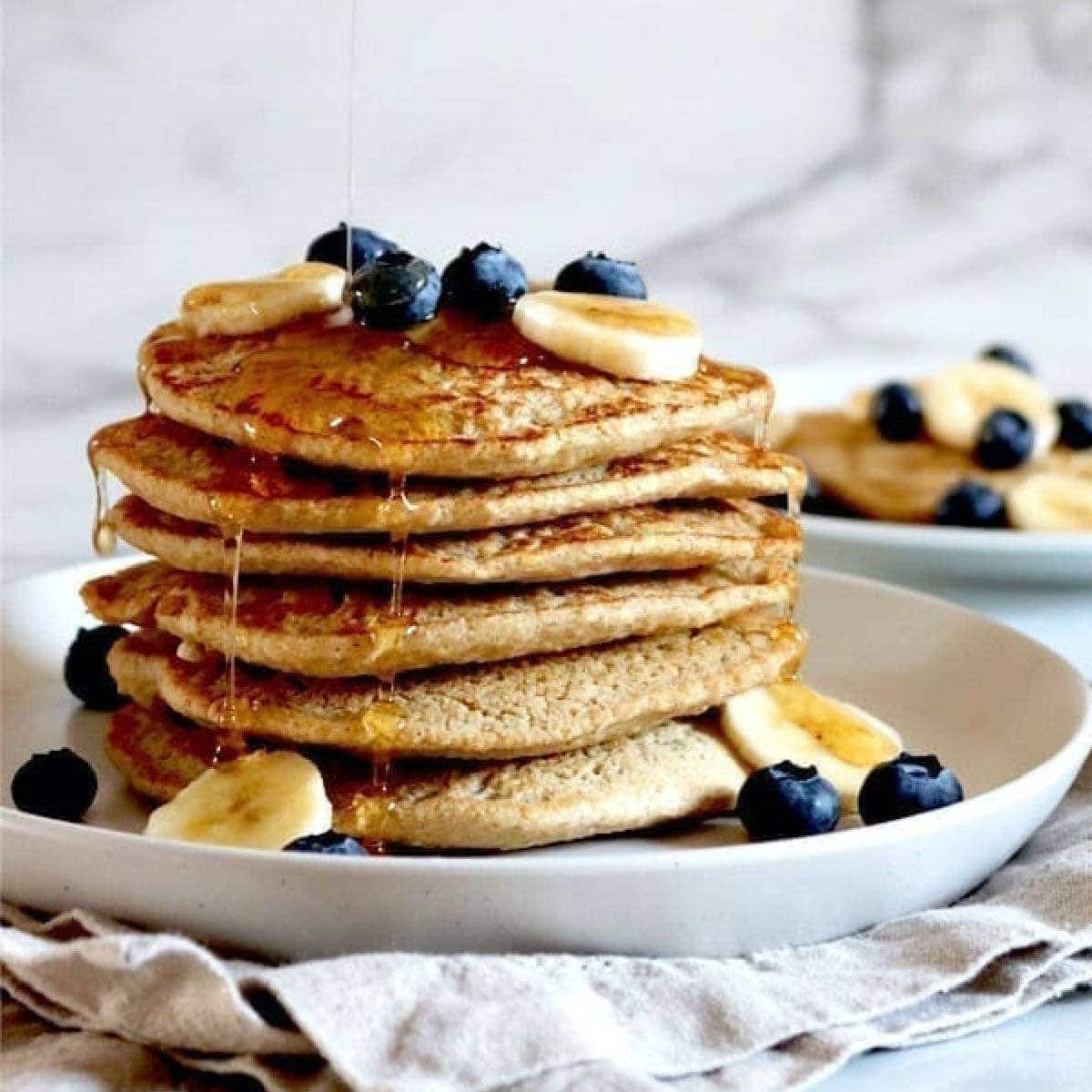 Stack of vegan oat pancakes topped with blueberries, bananas, and syrup.