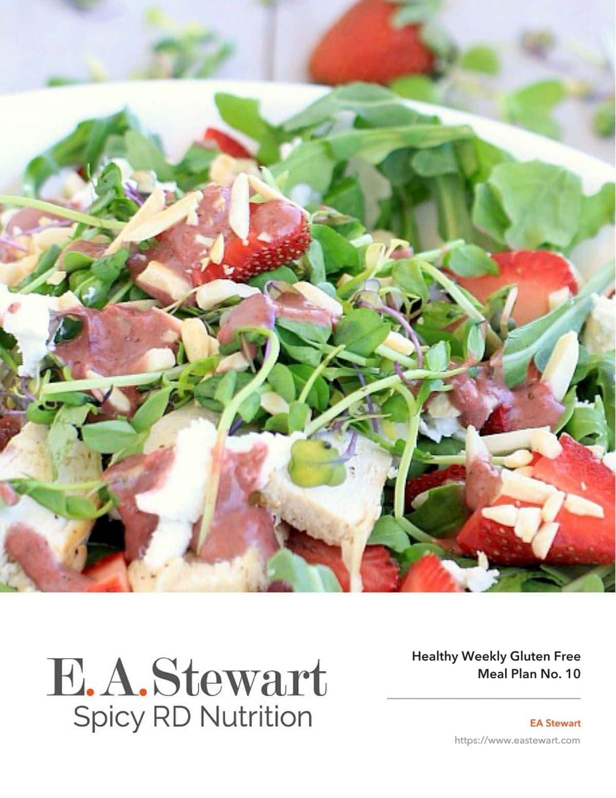 White plate with a strawberry arugula salad on top.
