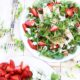 Plate of green, strawberries, and goat cheese salad.