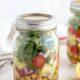 Greek Salad in a mason jar on a white background.