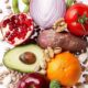 Picture of healthy food including avocado, apple, pomegranate, onion, tomato, kiwi, and beans.