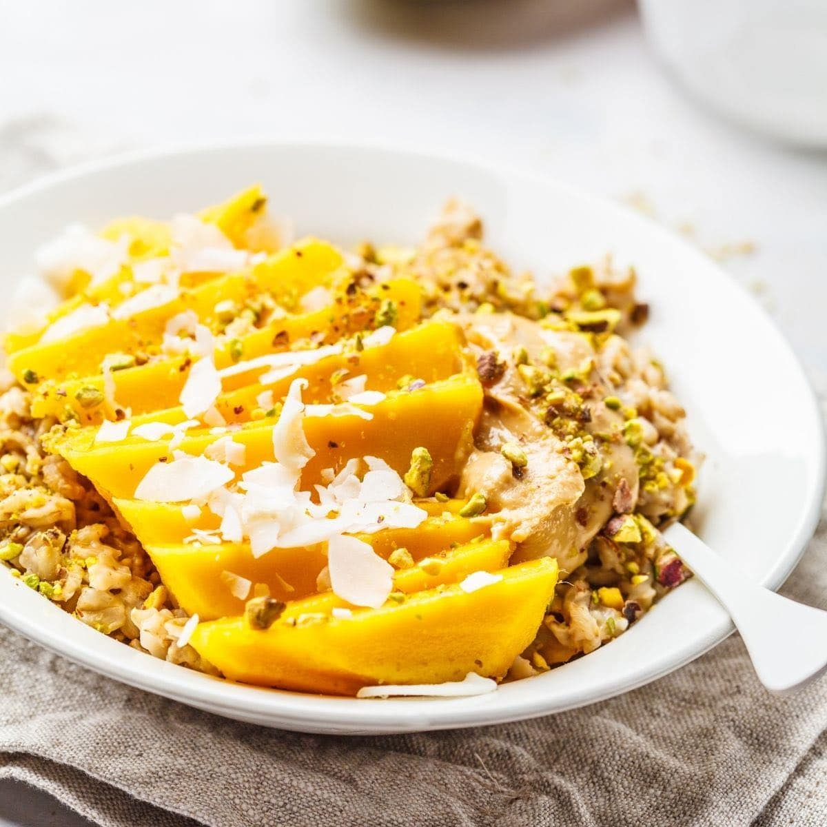 Bowl of oatmeal with mango slices and coconut.