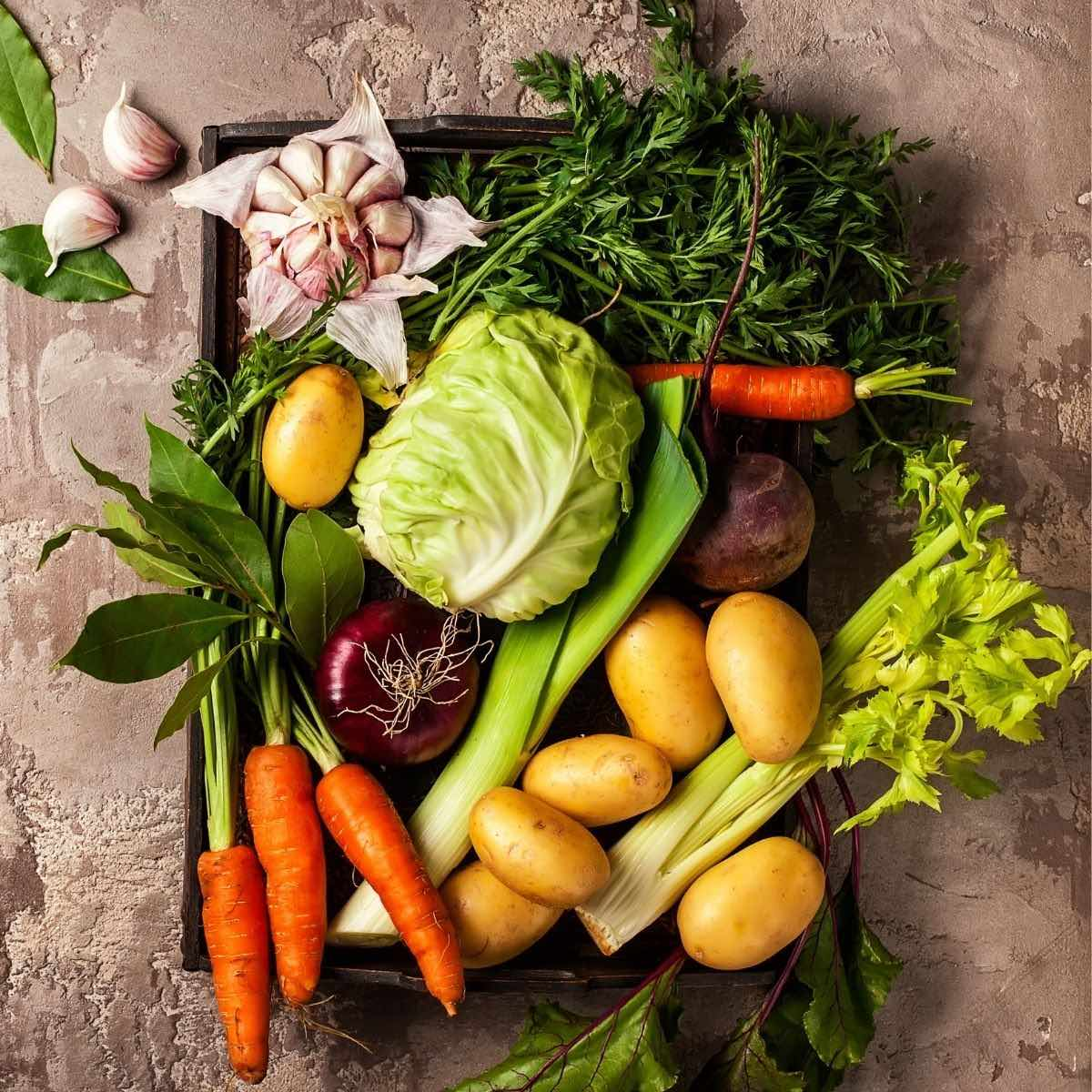 Overhead photo of a variety of vegetables, including carrots and potatoes, to eat on a low histamine diet.