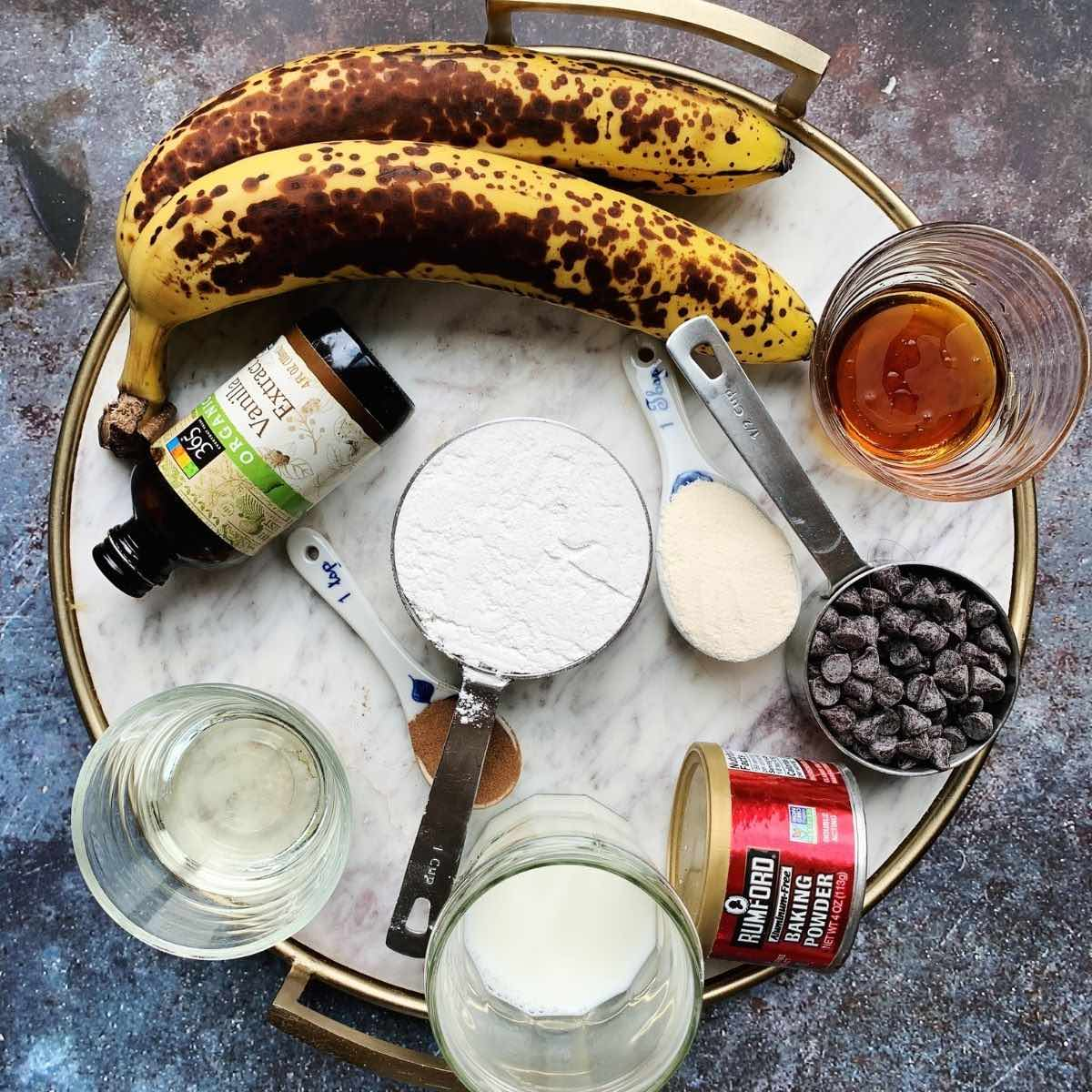 Ingredients on a white marble tray (banana, maple syrup, vanilla extract, gluten free flour, milk, chocolate chips, oil, baking powder).