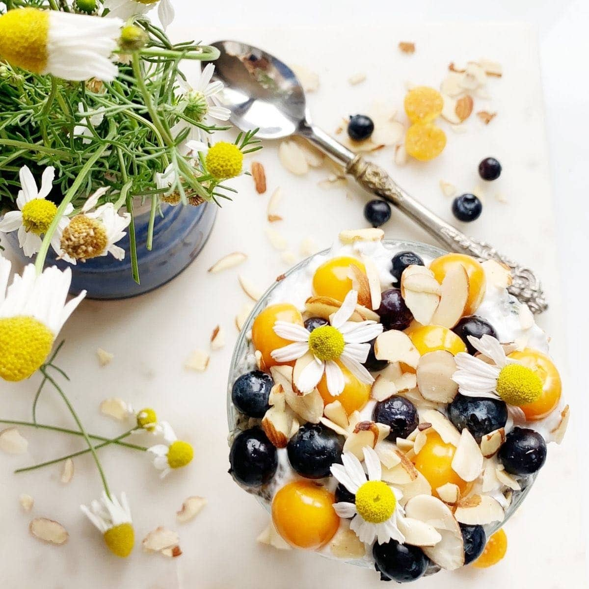 Overhead shot of golden berry chia parfait topped with blueberries, almonds, and chamomile flowers.