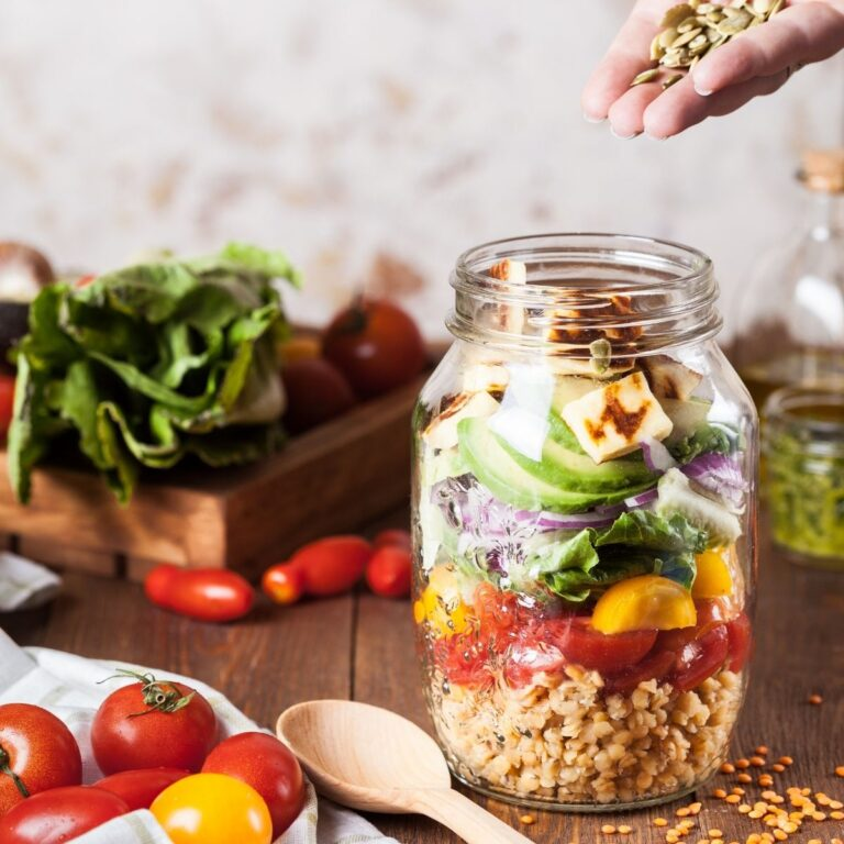 Mason jar salad with lentils, tomato, lettuce, tofu, and pumpkin seeds.