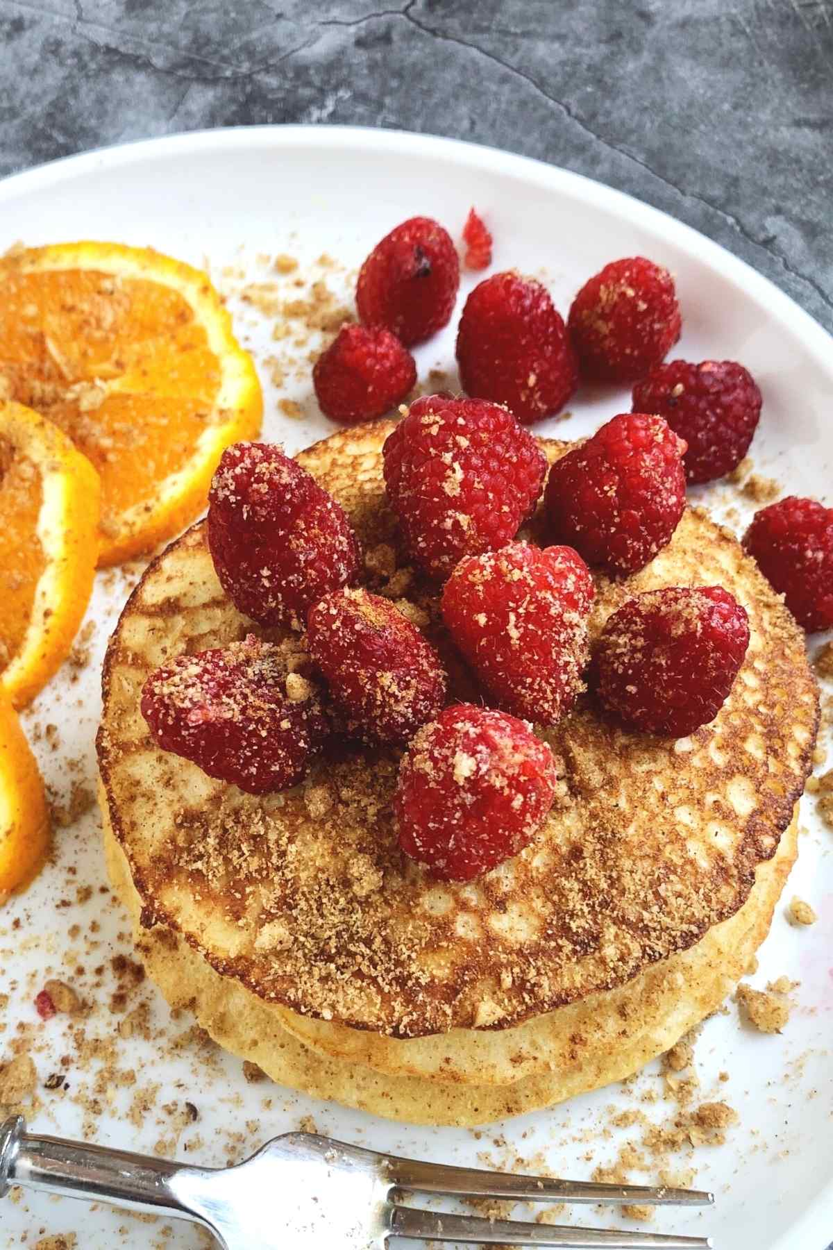 Stack of protein pancakes with raspberries on top. Fork in the foreground.