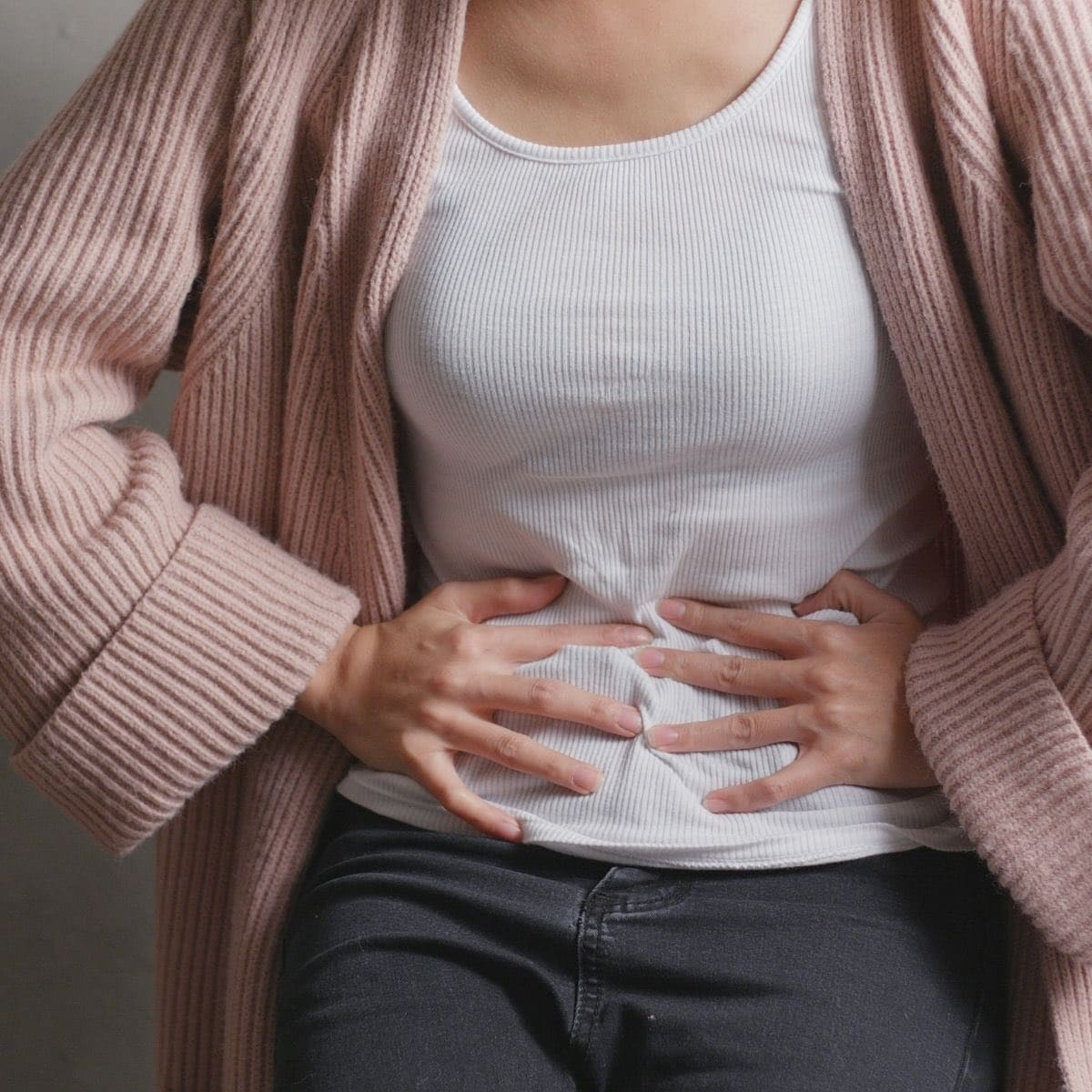 Photo of a woman in a pink sweater and white tank top holding her belly that's in pain from SIBO symptoms.